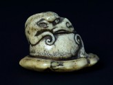Netsuke in the form of a rain dragon coiled around a mokugyō, a Buddhist percussion instrument