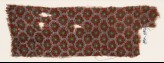 Textile fragment with grid of oval shapes and rosettes