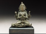 Seated figure of a crowned deity with four arms upon another figure