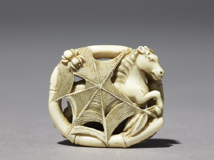 Netsuke depicting a horse caught in a spider's webfront