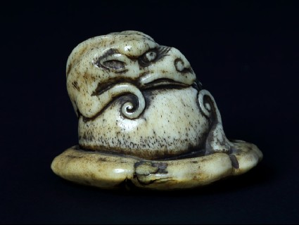 Netsuke in the form of a rain dragon coiled around a mokugyō, a Buddhist percussion instrumentfront