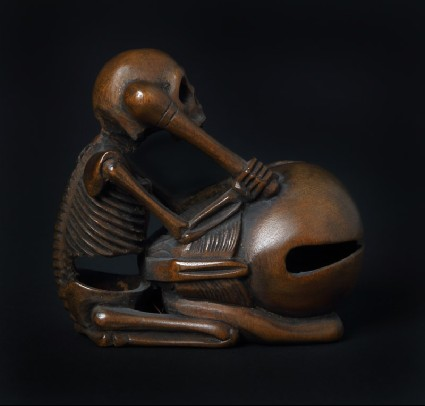 Netsuke in the form of a skeleton kneeling in front of a mokugyō, a Buddhist percussion instrumentfront