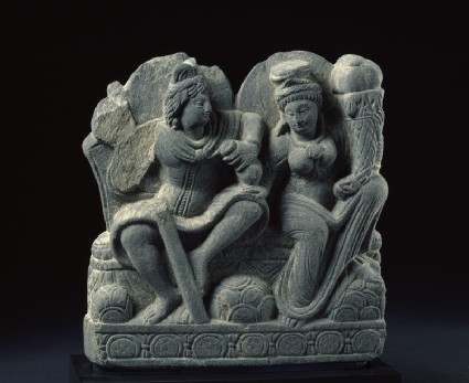 Relief depicting two deities with a staff, purse, and cornucopiaside