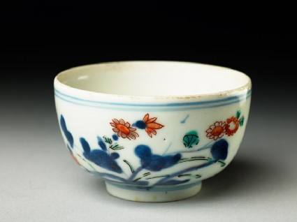 Cup with prunus and flowering plantoblique