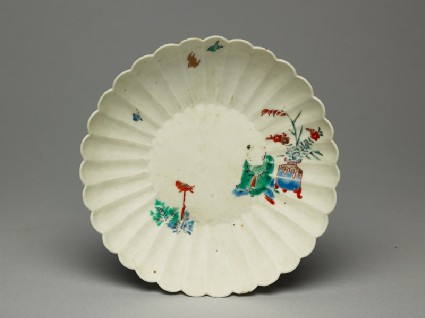 Fluted saucer depicting a boy, probably trying to catch a birdtop
