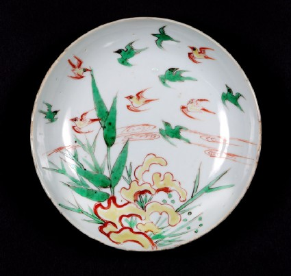 Dish with swallows flying over bamboofront