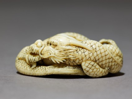 Netsuke in the form of a dragon coiled around a bowlside