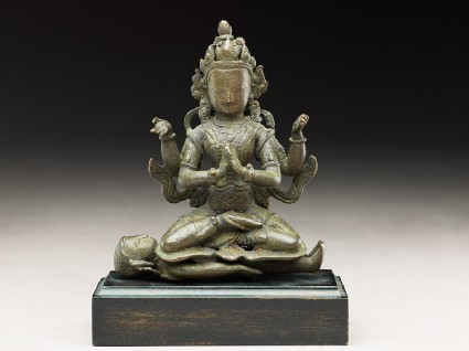 Seated figure of a crowned deity with four arms upon another figureside