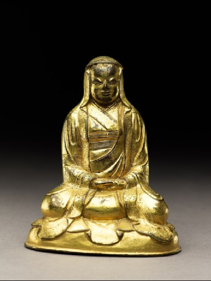 Seated figure of a monk with a robe draped over his headfront