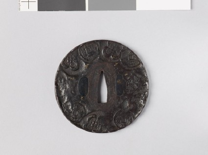 Round tsuba depicting old Chinese coins among mokkō shapes and scrollsfront