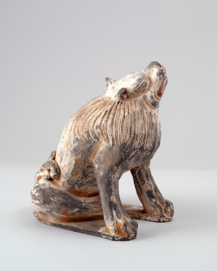 Figure of a lion scratching its headfront